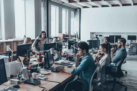 Photo pour Busy working day. Group of young business people concentrating at their work while sitting at the large office desk in the office together - image libre de droit