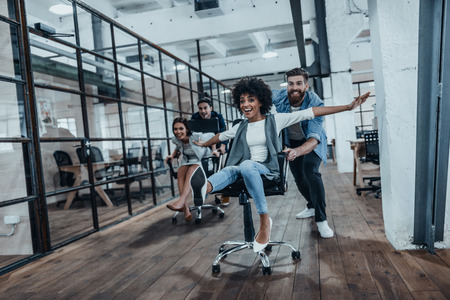 Foto de Office fun. Four young cheerful business people in smart casual wear having fun while racing on office chairs and smiling - Imagen libre de derechos