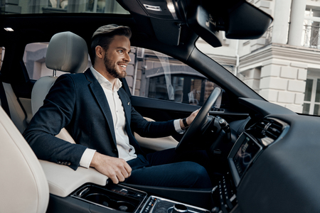 Photo pour Always in a hurry. Handsome young man in full suit smiling while driving a car - image libre de droit