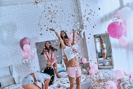 So happy! Four attractive young women in pajamas smiling and gesturing while jumping in the bedroom with confetti flying everywhere
