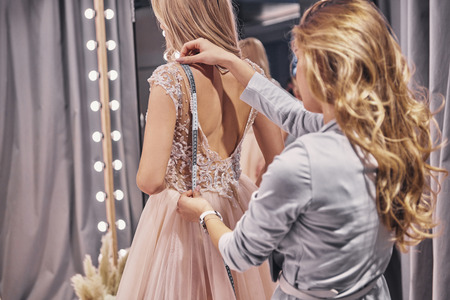 Photo pour Working on dress.  Young woman measuring bride while standing in the fitting room - image libre de droit
