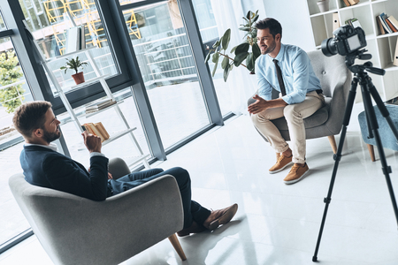 Foto de Business interview. Two young men in smart casual wear talking while making new video indoors - Imagen libre de derechos