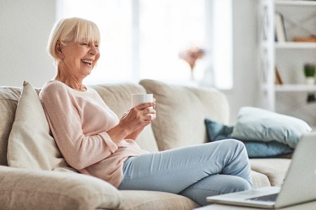 Lovely woman. Beautiful senior woman drinking coffee and smiling while relaxing on the couch at home