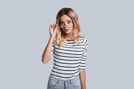 Photo pour Feeling curious. Attractive young woman adjusting her eyewear and looking at camera while standing against grey background - image libre de droit