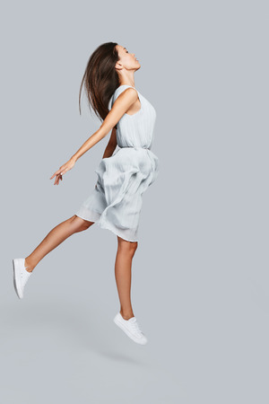 Photo for Zero gravity. Full length of beautiful young Asian woman hovering against grey background - Royalty Free Image
