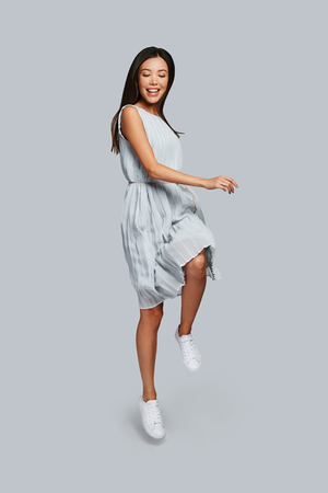 Playful. Full length of beautiful young Asian woman smiling while jumping against grey background