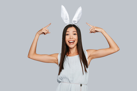 Photo for Look! Beautiful young Asian woman pointing at her bunny ears and smiling while standing against grey background - Royalty Free Image