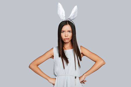 Photo for Bored bunny. Angry young Asian woman in bunny ears looking at camera while standing against grey background - Royalty Free Image