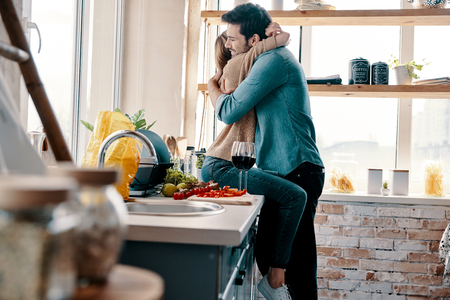 Photo for Love is more than just a game for two. Beautiful young couple cooking dinner and drinking wine while standing in the kitchen at home - Royalty Free Image