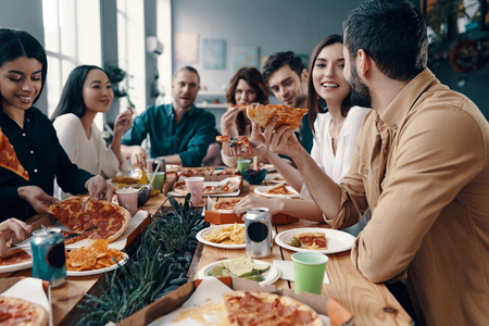 Photo for Holiday among friends. Group of young people in casual wear eating pizza and smiling while having a dinner party indoors - Royalty Free Image