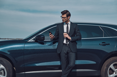 Photo pour Typing business message. Handsome young businessman using smart phone and drinking coffee while standing near his car outdoors - image libre de droit