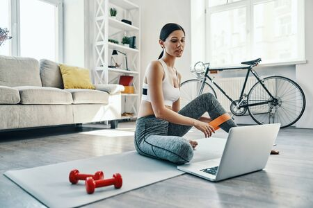 Photo pour Doing everything right. Beautiful young woman in sports clothing using laptop while exercising at home - image libre de droit