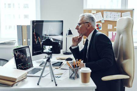 Photo pour Senior man in elegant business suit using modern technologies while making social media video - image libre de droit