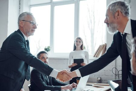 Photo for Modern businessmen shaking hands while working together with their team in the office - Royalty Free Image