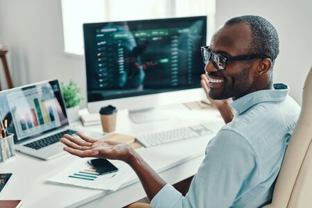 Foto de Handsome young African man in shirt using computer and smiling while working in the office - Imagen libre de derechos