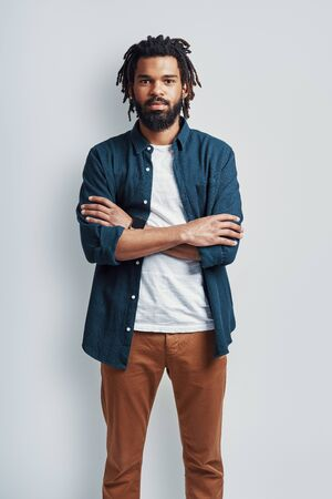 Photo pour Thoughtful young African man in casual wear looking at camera and keeping arms crossed while standing against grey background - image libre de droit