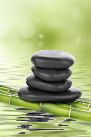 Zen basalt stones on bamboo on water