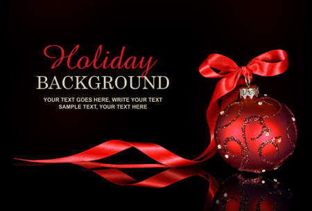 Photo pour Christmas background with a red ornament and ribbon on a black background - image libre de droit