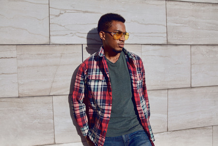 Photo for Stylish african man wearing red plaid shirt, looking away, guy posing on city street, gray brick wall background - Royalty Free Image