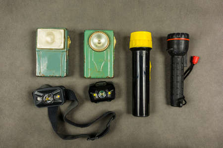 Different types of vintage and modern hand flashlights and headlamps.
