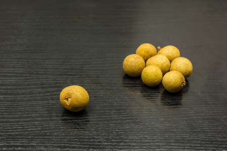 Ripe fruit of Dimocarpus longan on a wooden substrate.