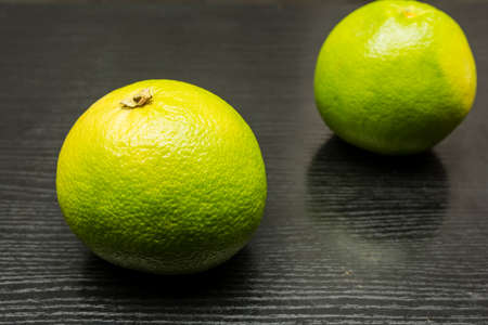 Green grapefruit variety on a wooden dark table.