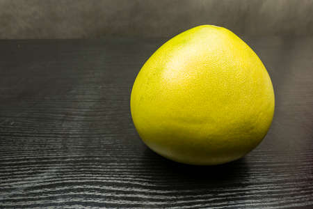 Ripe fruit of a citrus (Pomelo) on a wooden table.