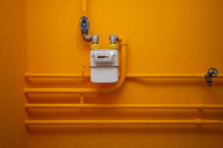 Photo for Pipes and gas-meter on orange wall - Royalty Free Image