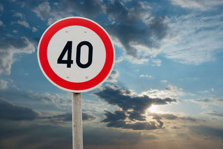 Speed limit traffic sign against cloudy sky