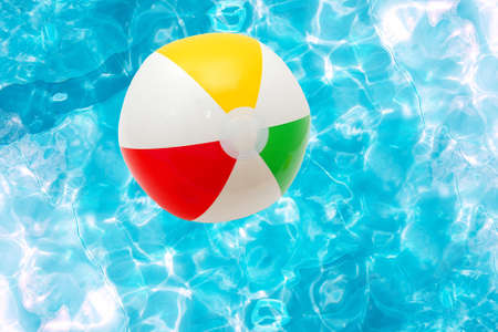 Beach ball over the water surface of a pool