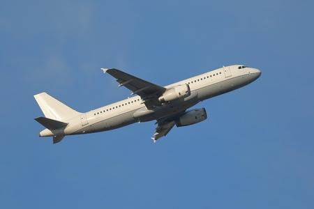 Foto de Airplane flying away to the blue sky - Imagen libre de derechos
