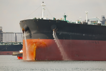 Photo for Large crude oil tanker ship pumping out ballast water when coming into port - Royalty Free Image