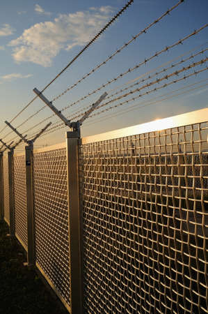 Metal fence Part of a metal grid fence with barbed wire at the top