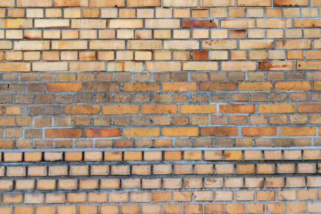 An old, antique dirty and repaired brick wall or wall frontally photographed as background or wallpaper
