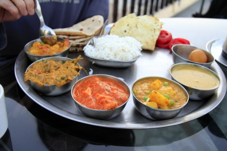 Traditional delicious north indian thali served in small metal bowls with rice and bread