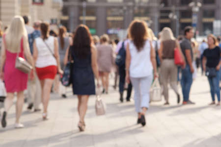 Photo pour people take a leisurely walk through the summer sunny city, a blurred background - image libre de droit