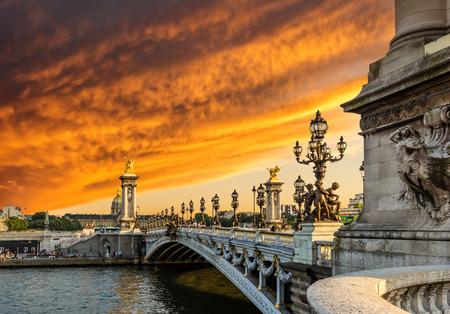 Photo pour Fantastic  sunset over Alexandre III bridge (Pont Alexandre III) and the National Residence of the Invalids, Paris, France - image libre de droit