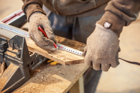 Photo for Construction Worker Using Tape Measure. Professional carpenter at work measuring wooden planks - Royalty Free Image