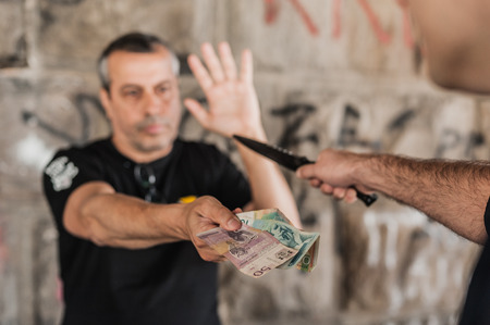 Photo pour Robber with knife taking money from victim in a abandoned part of the city - image libre de droit