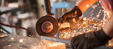 Photo for Electric wheel grinding on steel structure in factory. Sparks from the grinding wheel - Royalty Free Image