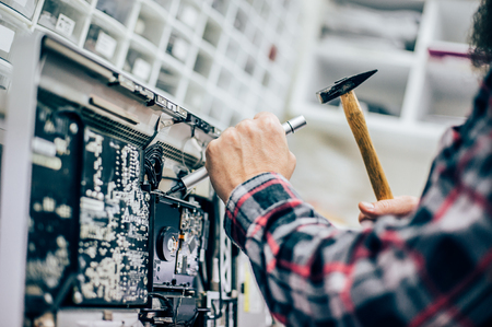 Funny electrician engineer repair faulty electric in computer monitor with hammer and screwdriver. Humor and fun concept