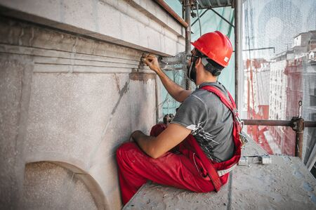 Photo pour Male worker plastering old building wall using cement plaster mix of cement and sand at the construction site - image libre de droit