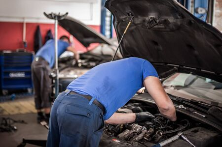 Photo pour Two car master auto mechanic repairers service technician checks and repairs the engine condition under the hood of the vehicle service shop - image libre de droit