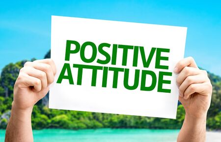 Hand holding cardboard with text Positive Attitude on island background