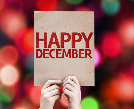 Hands holding cardboard with Happy December on bokeh background