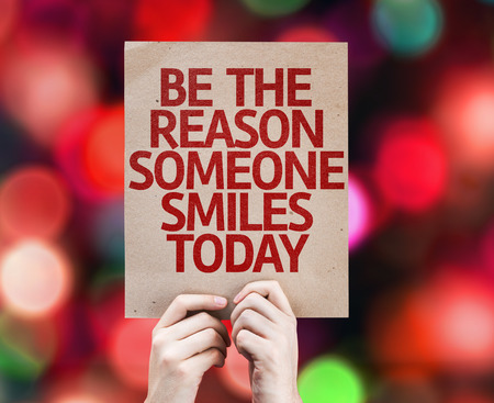 Photo pour Hands holding cardboard with Be The Reason Someone Smiles Today on bokeh background - image libre de droit