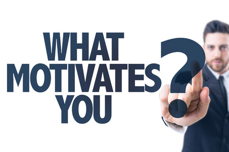 Business man pointing the text What Motivates You?