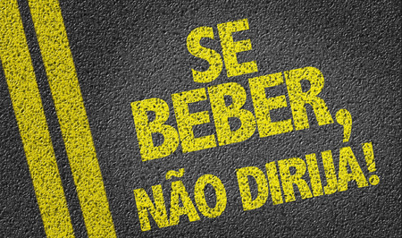 If You Drink Do Not Drive in Portuguese written on asphalt road
