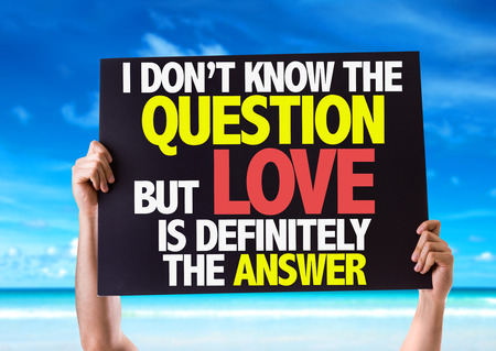Hands holding blackboard with I Don't Know The Question But Love Is Definitely The Answer on beach background