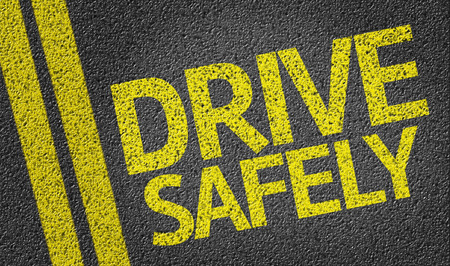 Text on tar road: Drive safely